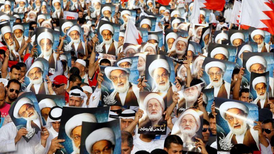 محتجون يحملون صورا لرجل الدين الشيعي البارز آية الله نعيم قاسم