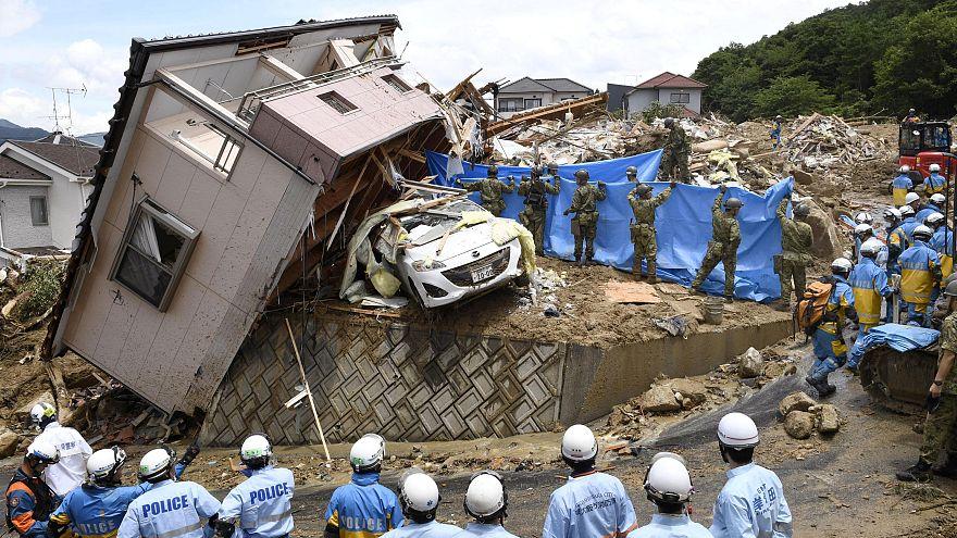 Rendőrök keresnek túlélőket egy ház romjai között Kumano városban