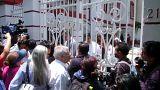 Mexikaner warten an weißem Gittertor auf Einlass