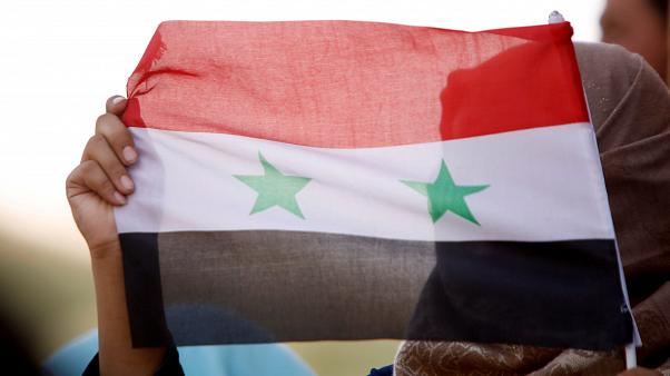 امرأة تحمل العلم السوري في درعا (4 تموز / يوليو)
