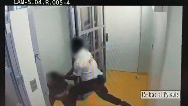 Ein Polizist drangsaliert einen Angeklagten im Türrahmen einer Zelle