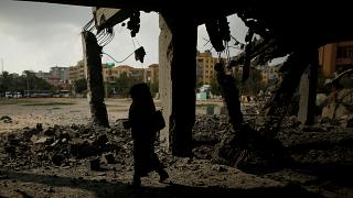Woman passes a building that was destroyed by Israeli air strike