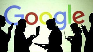 Des silhouettes vues devant le logo de Google