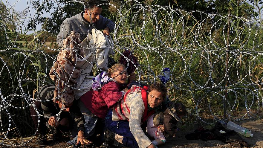 Syrian migrants cross under a fence as they enter Hungary