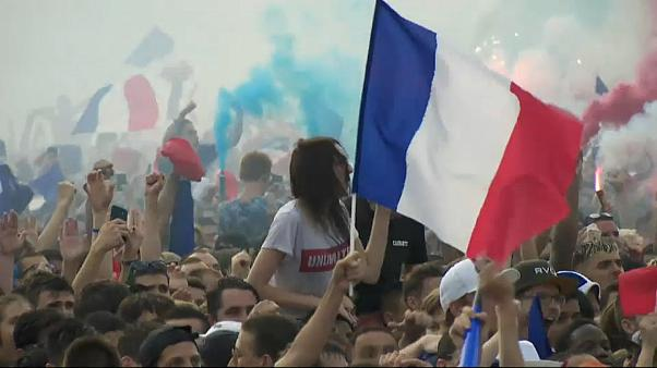 Une femme fêtent la victoire des Bleus dans la foule