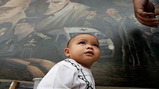 أمام رسم ضخم للأبطال الذين أنقذوا الصبية ومدربهم من الكهف