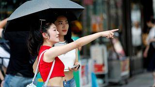 Deux jeunes femmes s'abritent du soleil au Japon durant une canicule