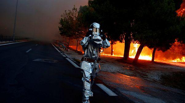 Un pompier en équipement lutte contre les incendies près d'Athènes, Grèce