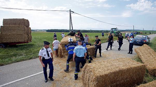 Police clear bales of straw from the path of the Tour de France