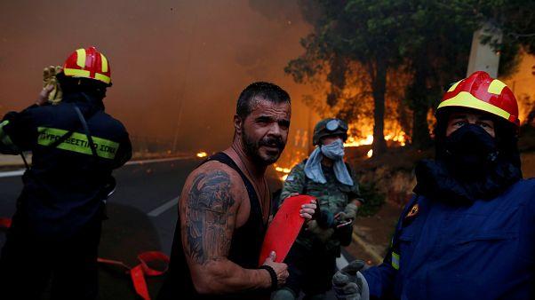Un habitant combat le feu auprès des pompiers en Grèce