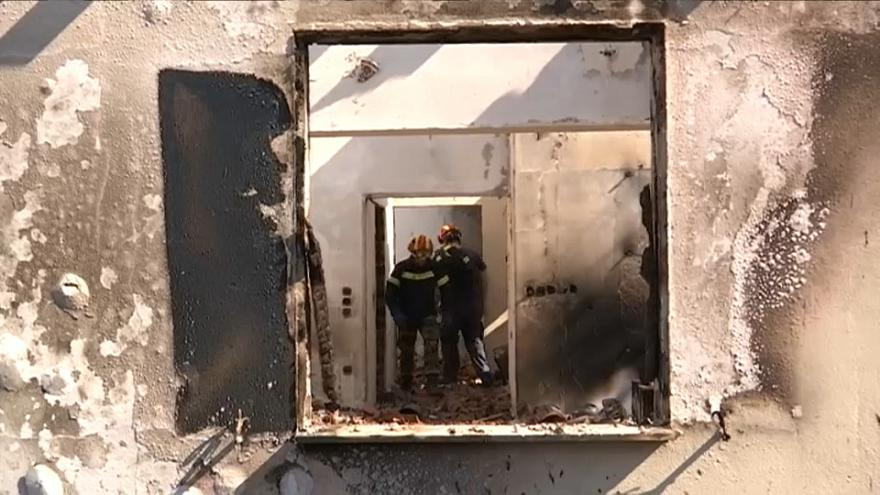 Des pompiers visitent une maison détruite par les incendies en Grèce