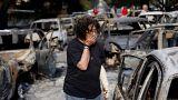 Egy nő a kutyáját keresi Matiban a tűzvész után