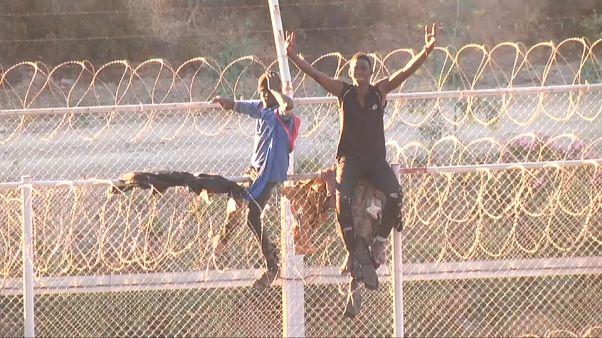 Des migrants sur la barrière entre le Maroc et l'enclave espagnole de Ceuta