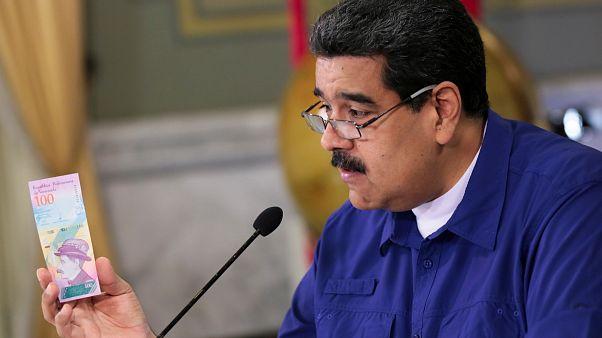 الرئيس الفنزويلي نيكولاس مادورو يمسك ورقة نقدية من عملة بلاده البوليفار