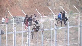مهاجرون يتسلقون السور الحدودي