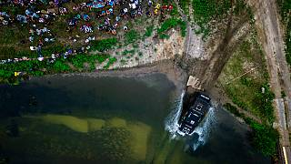 Vogelperspektive: Ein Truck fährt in ein Gewässer, viele Menschen schauen