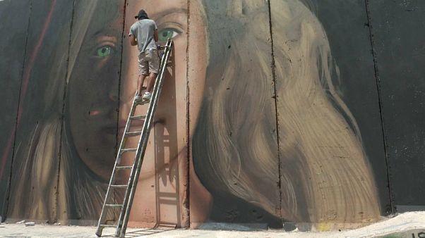 ( Lo street artist italiano mentre esegue un murale di Tamimi a Betlemme)