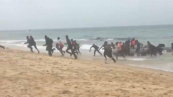 شاهد لحظة وصول مهاجرين أفارقة  إلى شاطئ سياحي في إسبانيا وسط دهشة المصطافين