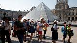 سياح صينيون أمام هرم متحف اللوفر في العاصمة باريس