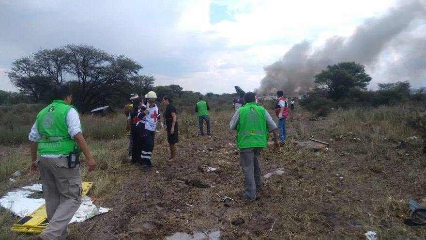 Rettungskräfte helfen Passagieren in der Nähe der Absturzstelle.