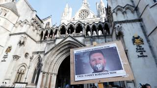 A poster supporting Tommy Robinson outside the High Court in London