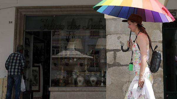 Turista passeia protegida por uma sombrinha em Évora