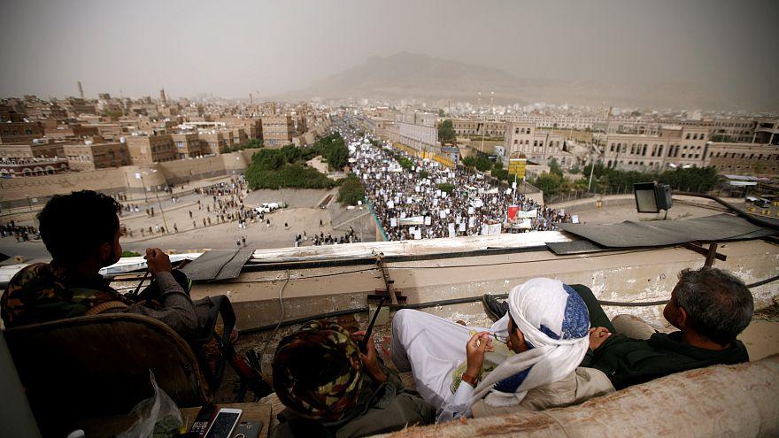 جنود حوثيون يشاهدون مسيرة لمناصريهم بصنعاء
