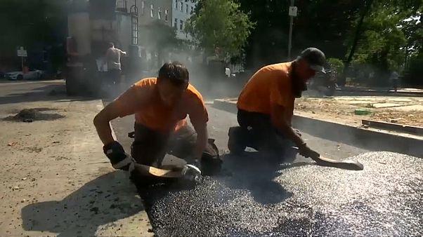Ein echter Knochenjob: Heißen Asphalt auf der Straße verteilen.