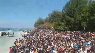 Menschen warten am Strand auf ihre Rettung