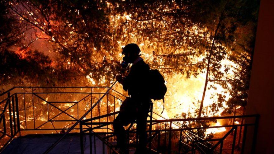 متطوع يرش المياه على حريق غابات في بلدة رافينا قرب أثينا في اليونان ي