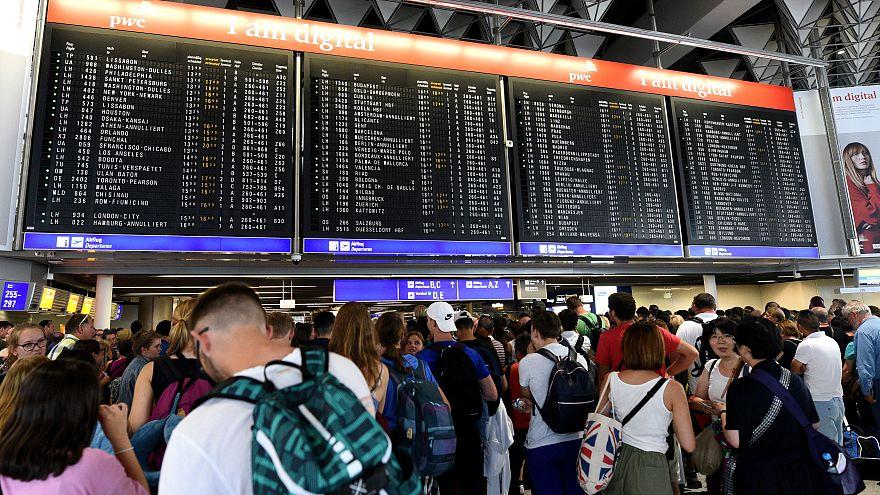 Reisende warten am Flughafen Frankfurt vor der Anzeigetafel