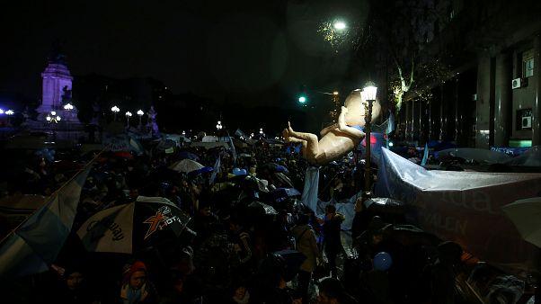 Eine überdimensionale Babyfigur wird von Demonstranten getragen