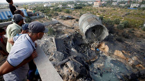 فلسطينيون ينظرون إلى الدمار الذي سببه القصف الإسرائيلي ببلدة المغراقة بغزة