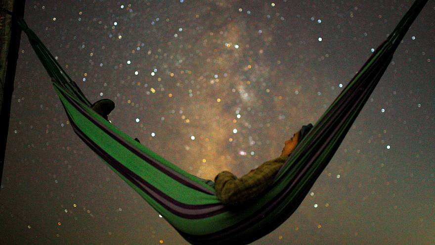 A girl lies in hammock as she looks at the milky way in Kozjak, Macedonia
