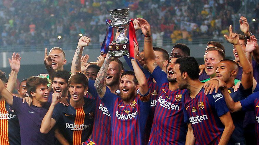 لاعبو فريق برشلونة يرفعون كأس السوبر الإسبانية بعد فوزهم على أشبيلية