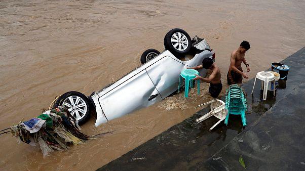 Einwohner reinigen Stühle neben einem überfluteten Auto