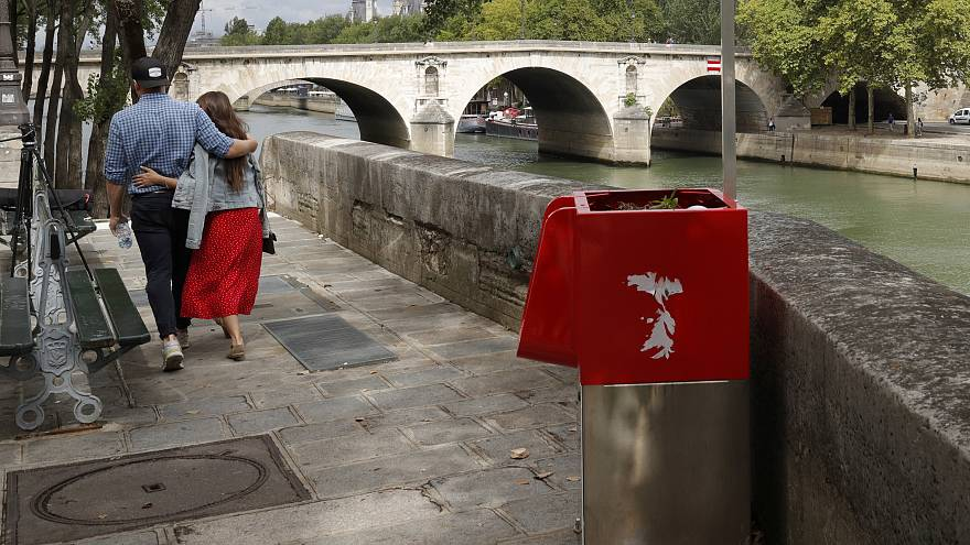 A couple walks near eco-friendly urinal on the Ile Saint-Louis