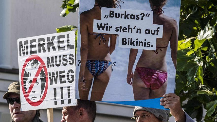 """""""Burka? Biz bikiniyi tercih ederiz"""" ve """"Merkel ayrılmalı"""" yazılı posterler"""