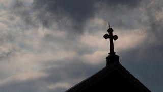 Kreuz auf Kirchendach vor dunklen Wolken