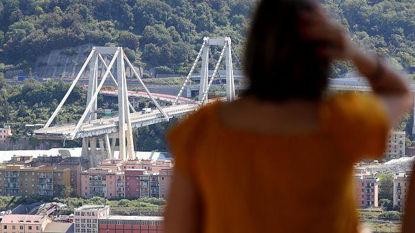 Eine Frau blickt auf die eingestürzte Brücke in Genua