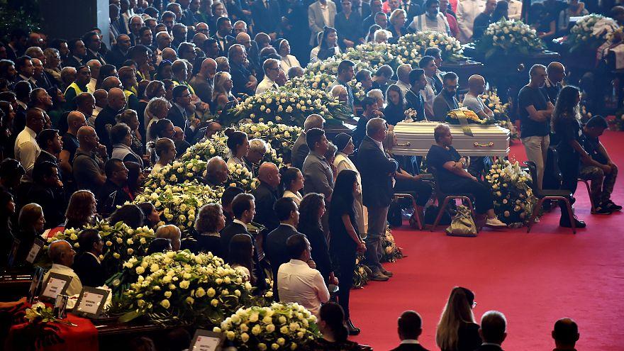 Mit Blümen geschmückte Särge bei der Trauerfeier