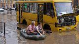 Paddelboot vor gelbem Bus auf überfluteter Straße