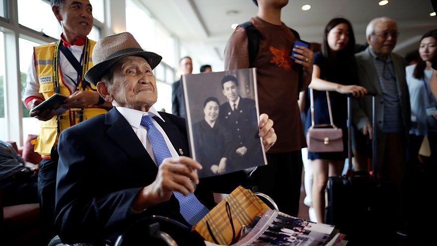 Ein älterer Mann hält ein Bild seiner Verwandten hoch