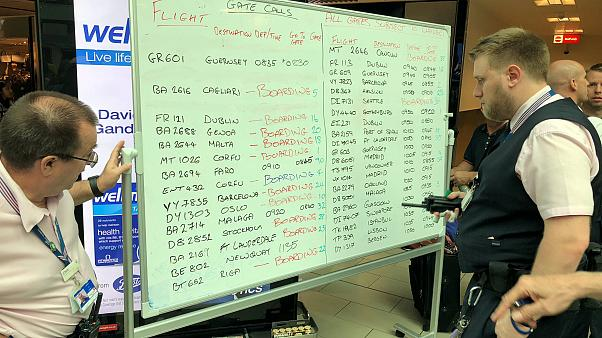 Gatwick staff display flight information on a whiteboard on August 20, 2018