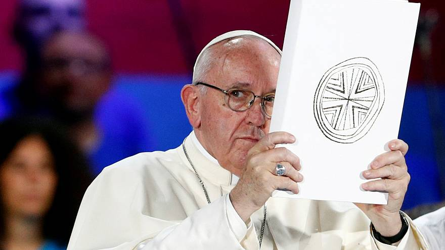 File photo: Pope Francis holds the Book of the Gospels