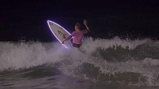Watch: Surfers catch waves under moonlight