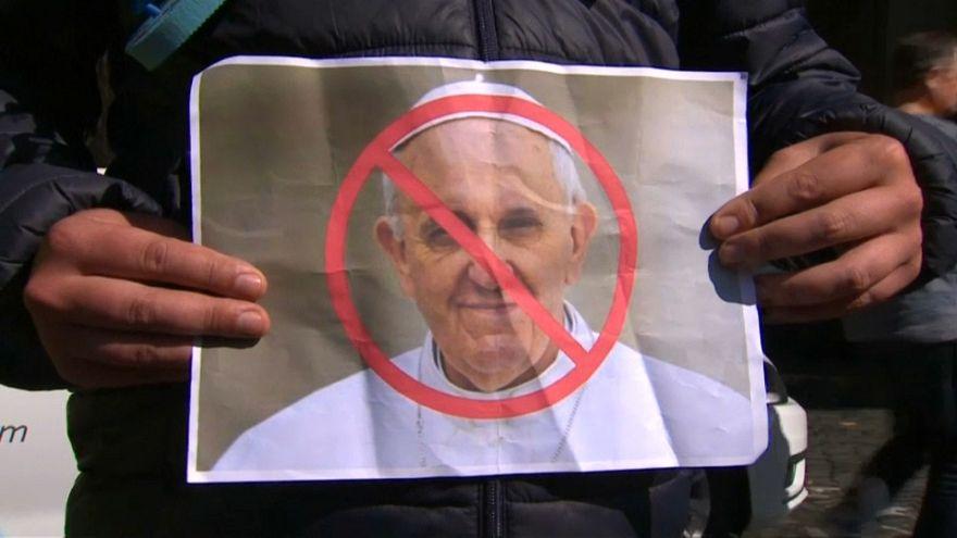 محتجون يحملون أحذية أطفال وأعلام قوس قزح للتظاهر ضد البابا فرانسيس في أيرلندا