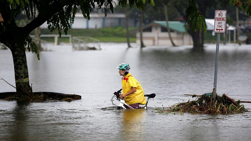 امرأة تدفع دراجتها عبر الفيضانات الناجمة عن إعصار لين في هيلو - رويترز