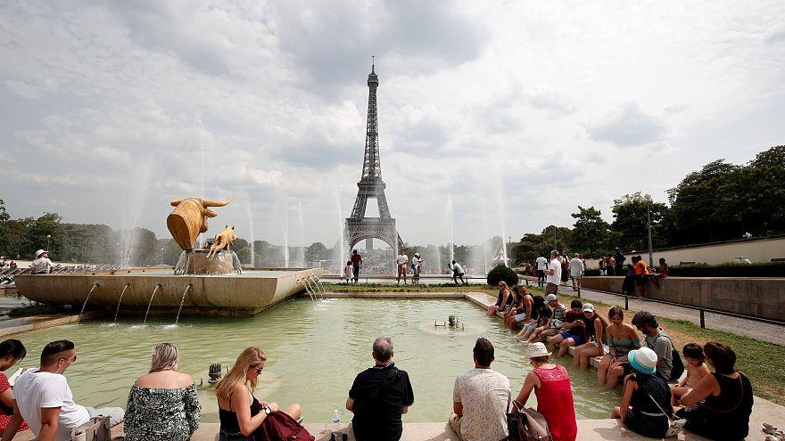 Des touristes au bord d'une fontaine non loin de la Tour Eiffel à Paris