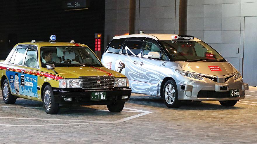 Egy hagyományos és egy önvezető taxi Tokióban